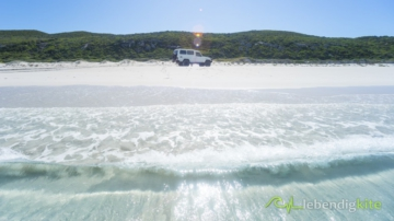 crystal clear waves and 4x4 4WD driving on the beach in soft sand