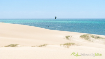 flat water kiting at a beach with sand dunes