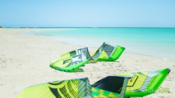 green Cabrinha Kite FX and Drifter on the beach with blue water