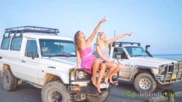 two girls on the bonnet of a Landcruiser Troopcarriers, a Nissan Patrol in the background