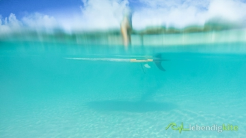 SUP Stand Up Paddle Board under water in blue crystal clear water