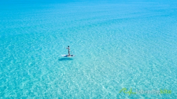 SUP Stand Up Paddle Boarding in crystal clear blue water in Australia